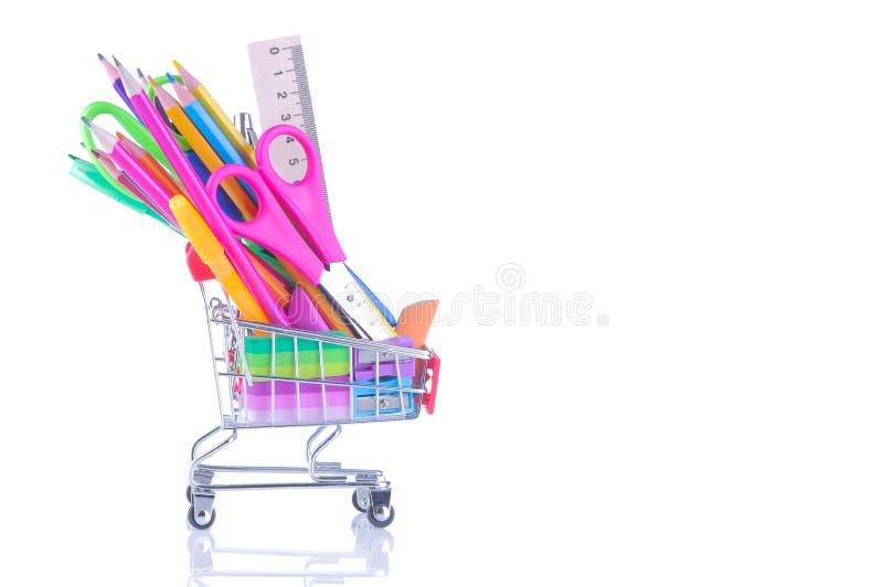 olika färgrika skolatillförsel i en shoppingspårvagn på en vit isolerade bakgrund royaltyfria foton