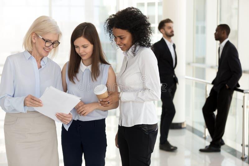 Olika företagsanställda som har tillfälliga samtal i företagshall royaltyfria foton