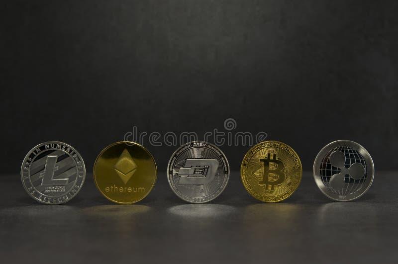 Olika faktiska mynt på svart royaltyfria bilder