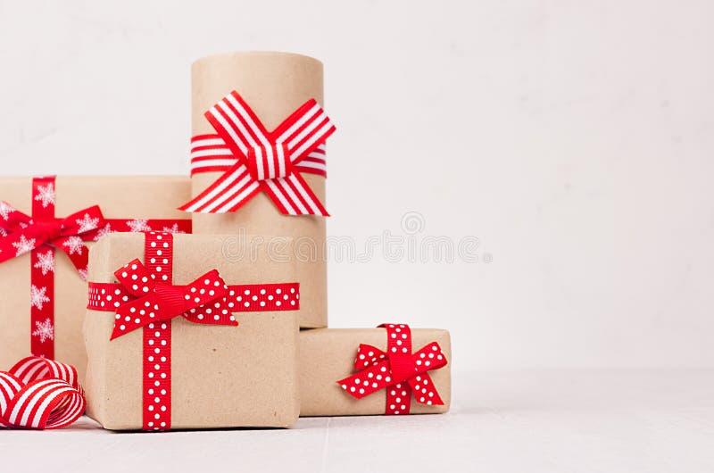 Olika festliga gåvaaskar för hög med röda band och pilbågar på den vita trätabellen med kopieringsutrymme, closeup royaltyfri foto