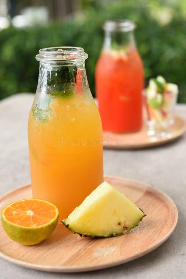 Olika flaskor av fruktsaft med frukter royaltyfria bilder