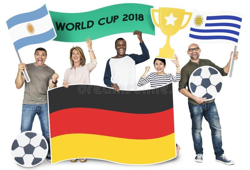 Olika fotbollsfan som rymmer flaggorna av Argentina, Tyskland och Uruguay arkivfoto