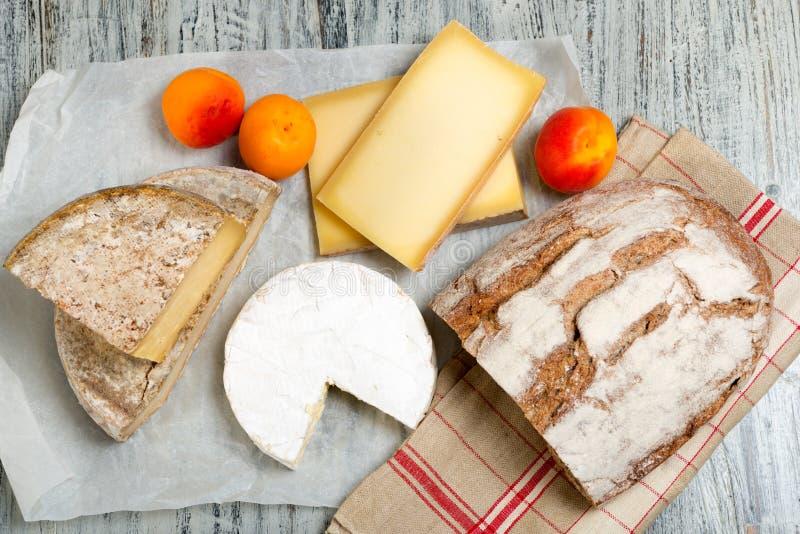 Olika franska ostar med bröd och aprikors royaltyfria bilder