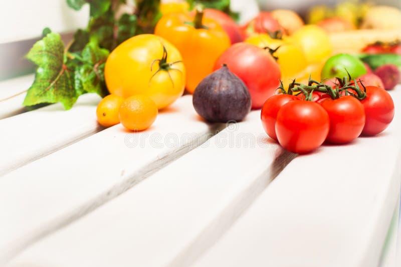 Olika frukter och grönsaker spridda på den ent vita bänken arkivbild