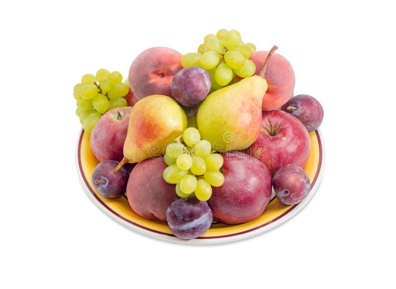 Olika frukter på den stora gula maträtten royaltyfri foto