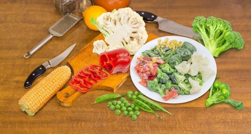 Olika fryste och nya grönsaker på en matlagningtabell royaltyfria foton