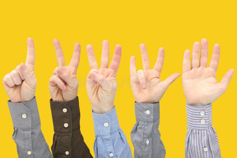 Olika gester av manliga h?nder mellan de p? en gul bakgrund arkivbild