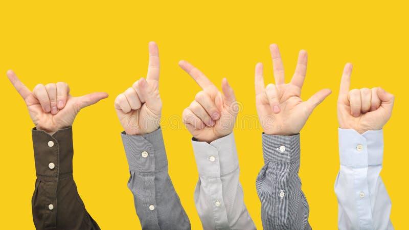 Olika gester av manliga h?nder mellan de p? en gul bakgrund royaltyfri fotografi