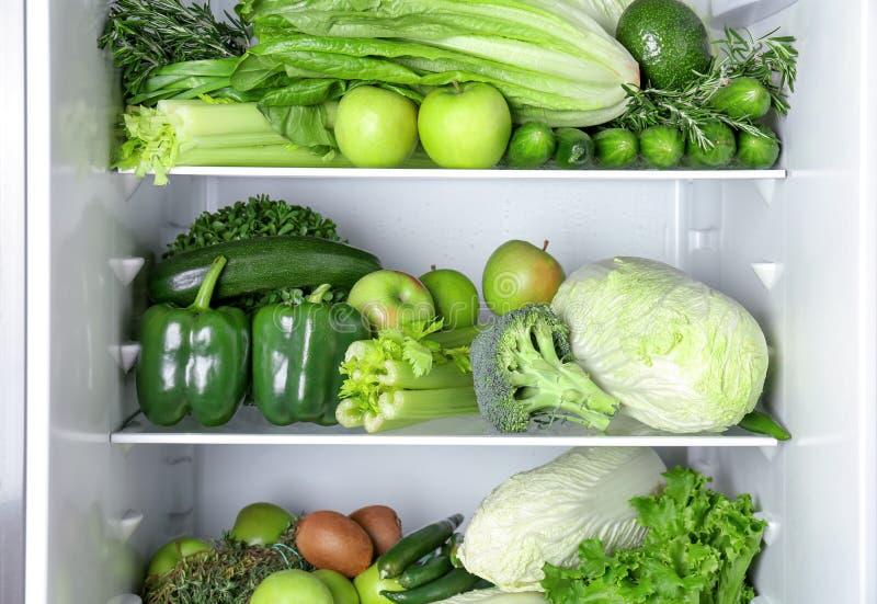 Olika gröna grönsaker och frukter på hyllor royaltyfri foto