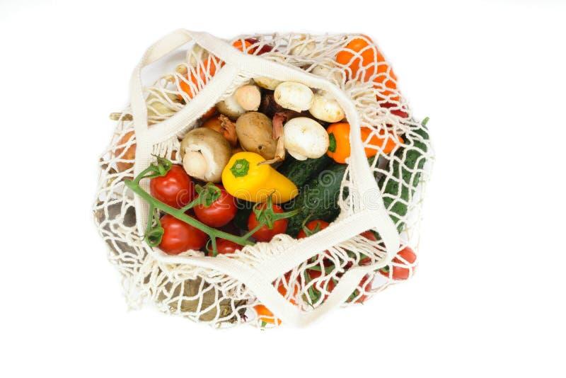 Olika grönsaker i netto påse för vitt ingrepp och som isolerar på vit bakgrund arkivbilder