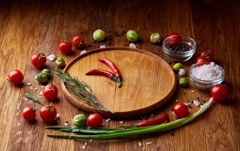 Olika grönsaker, smaktillsats och spicies runt om den tomma plattan på lantlig träbakgrund, bästa sikt fotografering för bildbyråer