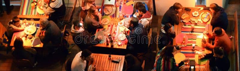 Olika grupp människor som tycker om en utomhus- matställe i en restaurang arkivfoton