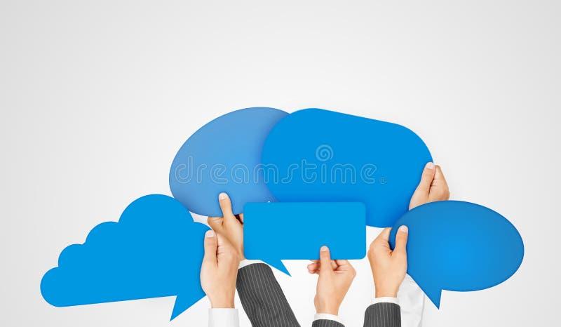 Olika händer som rymmer blåa anförandebubblor arkivbild