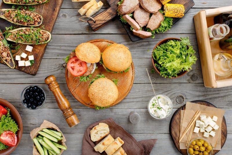 Olika hamburgare, biff och grillade grönsaker arkivbild