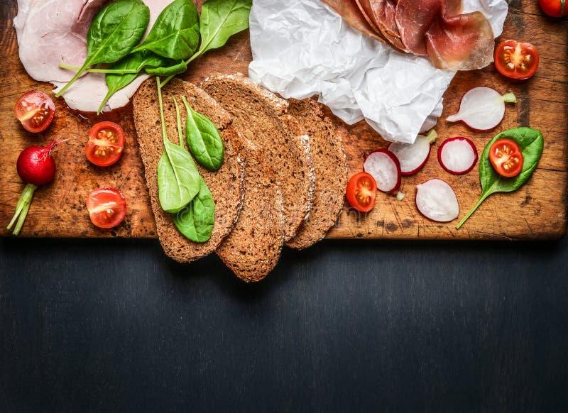 Olika ingredienser för kött och skinksmörgås på mörk träbakgrund fotografering för bildbyråer
