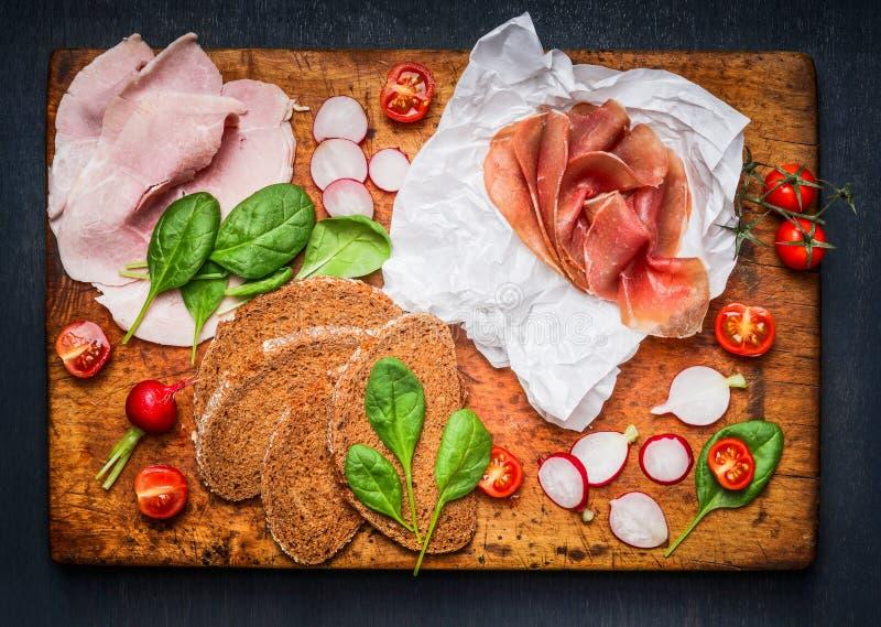 Olika ingredienser för smaklig smörgås med skinka och rökt kött på lantlig skärbräda royaltyfri foto