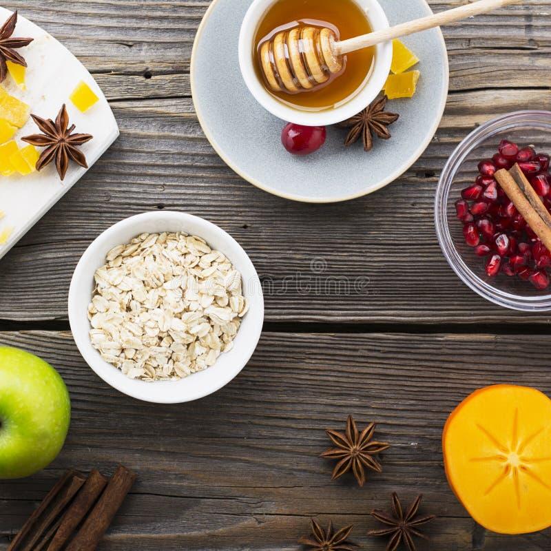 Olika ingredienser för stekheta för vinter säsongsbetonade och andra recept, granatäpple, honung, orezhi, äpplen, persimoner, ört royaltyfria bilder