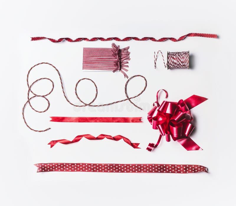 Olika julband och pilbågar för garnering- och gåvainpackning och att förpacka på vit bakgrund arkivfoton
