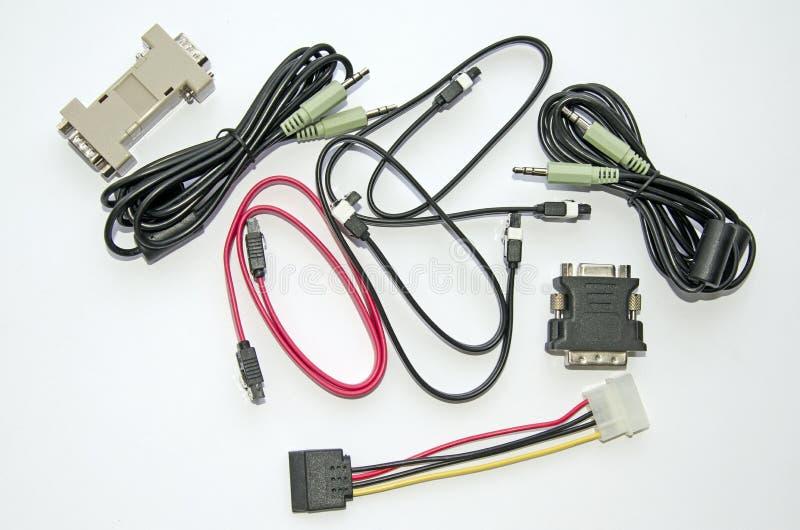 Olika kablar och adapter för persondatorn på en grå färgbakgrund arkivfoto