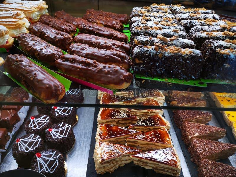 Olika kakor med piskad kräm och choklad - kakor royaltyfri bild