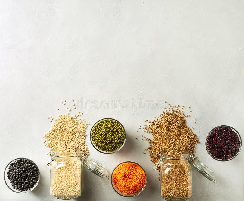 Olika korn och bönor, inklusive ris, buckweat, linser, Mung bönor i exponeringsglaskrus på tabellen i köket royaltyfri bild