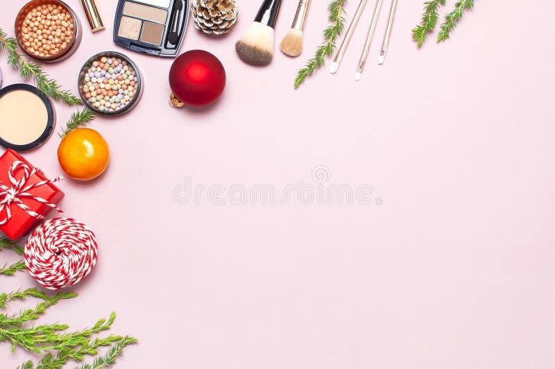 Olika kosmetiska produkter för smink, rouge, pulver, borstar, läppstift, ögonskugga och julgåvan, granfilialer arkivfoto