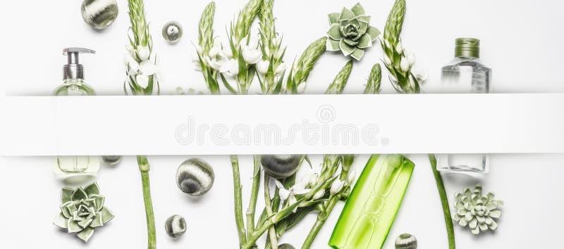 Olika kosmetiska produkter med gröna blommor och växter på vit bakgrund, ram royaltyfria bilder