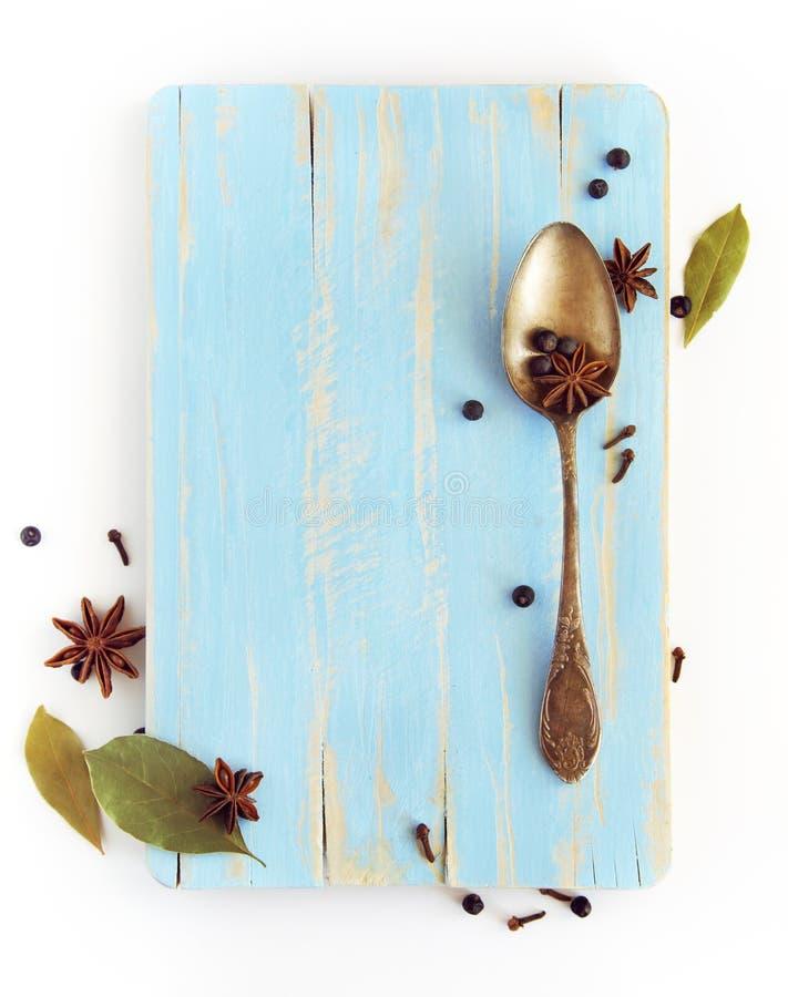 Olika kryddor, anis, lager, kryddnejlika och andra på en träbo royaltyfri bild