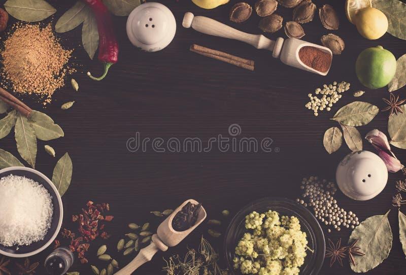 Olika kryddor för bakgrund på tabellen liksom kokosnöten, jordningspeppar i en sked för kryddor, Hypericum, gurkmeja, lagerbladar royaltyfria bilder