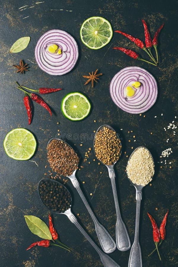 Olika kryddor i skedar, koriander, sesamfrö, lin kärnar ur, pepparkorn på en mörk bakgrund Skivor av den röda löken och limefrukt royaltyfria foton