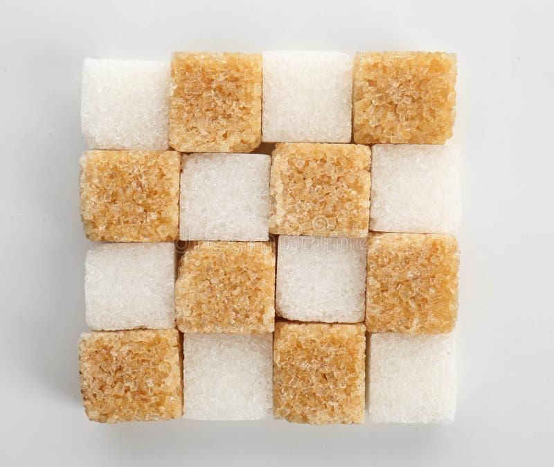 Olika kuber av socker på vit bakgrund arkivfoto
