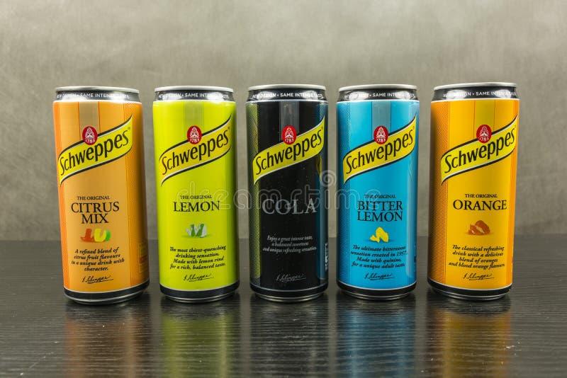 Olika kulöra cans med olika anstrykningar av kolsyrade drycker som göras av Schweppes royaltyfri foto