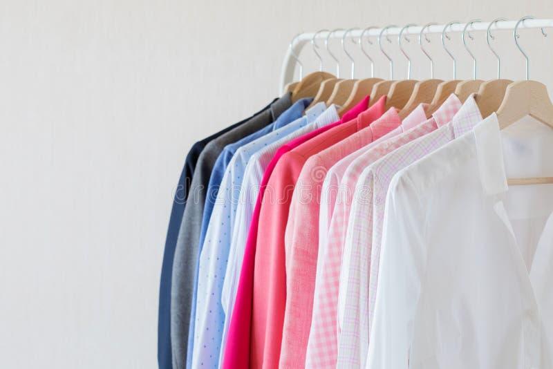 Olika kulöra skjortor som hänger på kuggen fotografering för bildbyråer