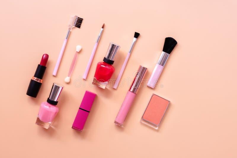 Olika kvinnamakeupskönhetsmedel på en pastellfärgad rosa bakgrund Rouge läppstift, spikar polermedel och borstar B?sta sikt, lekm royaltyfria foton