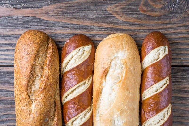 Olika Loaves av bröd på lantligt trä royaltyfri fotografi
