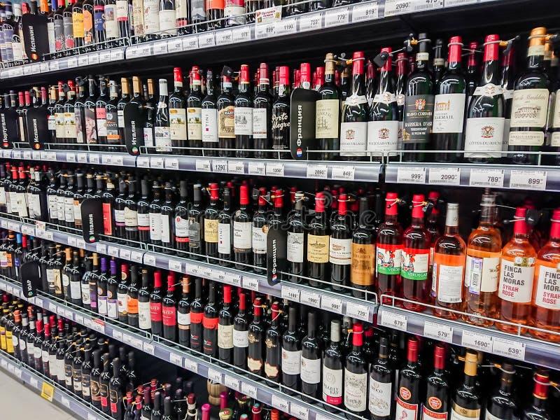 Olika märken av rött och rosa vin på hyllorna av supermarket royaltyfri fotografi
