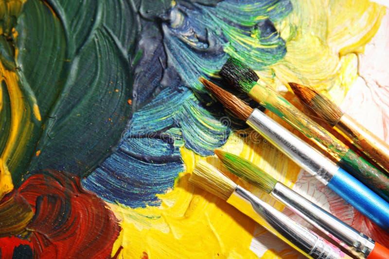 Olika målarfärgborstar på kanfas, bästa sikt arkivbild