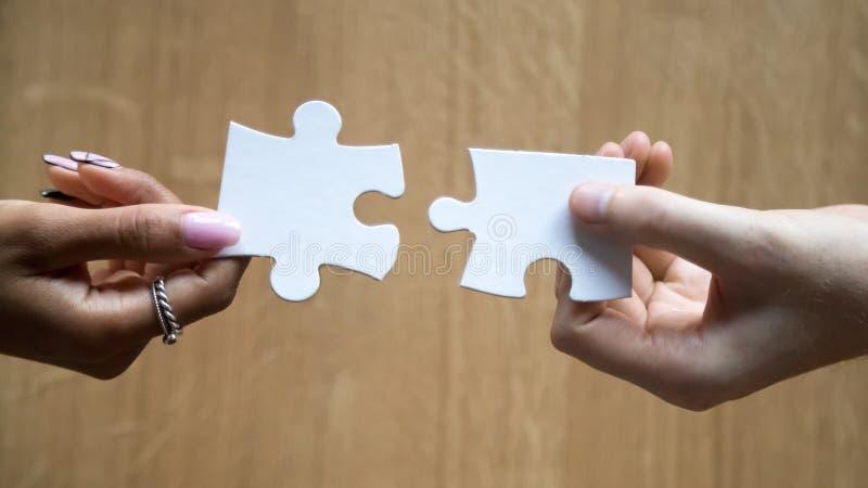 Olika man- och kvinnahänder som rymmer sammanfogande stycken som förbinder pusslet arkivfoton