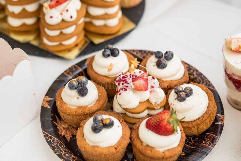 Olika mini- kakor Sötsaker dekorerade med nya bär för ferie smaklig cake små kakor med olika bär och arkivfoto