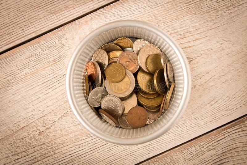 Olika mynt i en metallkorg övre sikt Begreppet av armod Begreppet av besparingar arkivbilder