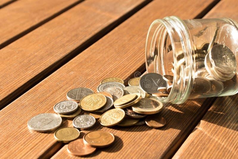 Olika mynt sprids på en trätabell Begreppet av po royaltyfri bild