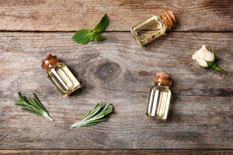 Olika nödvändiga oljor i glasflaskor och ingredienser på träbakgrund arkivfoton