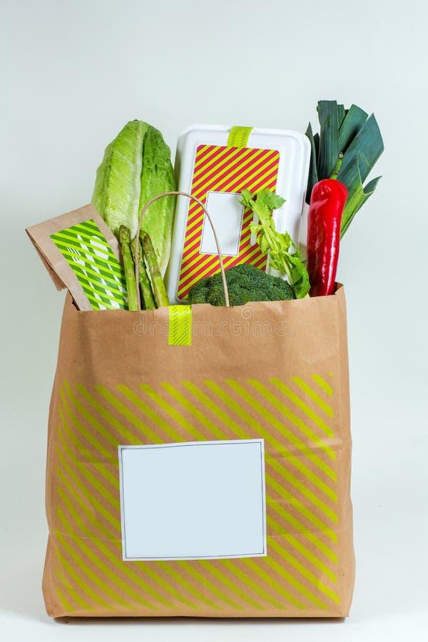 Olika nya gräsplaner, grönsaker och vit ask i pappers- påse arkivfoto