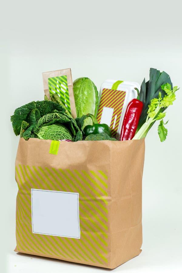 Olika nya gräsplaner, grönsaker och vit ask i pappers- påse arkivfoton