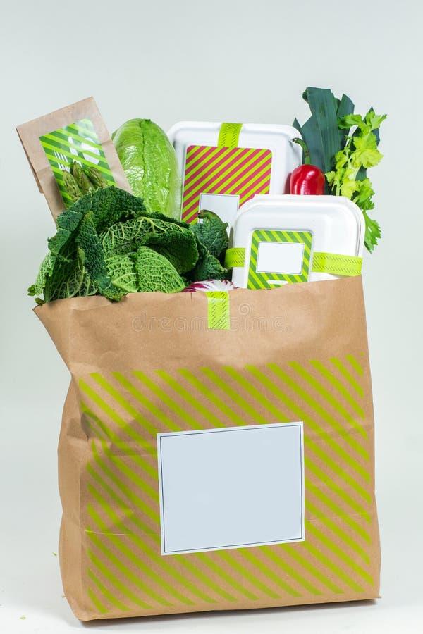 Olika nya gräsplaner, grönsaker och vit ask i pappers- påse royaltyfria bilder