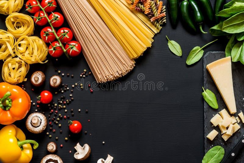Olika nya ingredienser för att laga mat italiensk pasta, spagetti, fettuccine, fusilli och grönsaker på en svart arkivbilder