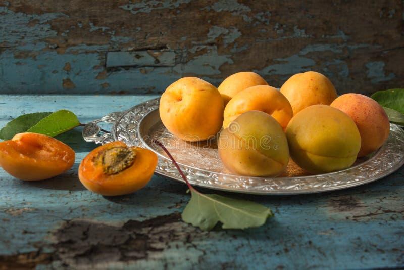 Olika nya mogna aprikors på träaprikors för yttersidasidafrukter klippte ombord aprikors i halva Ljus - blå lantlig wood backgro arkivbild