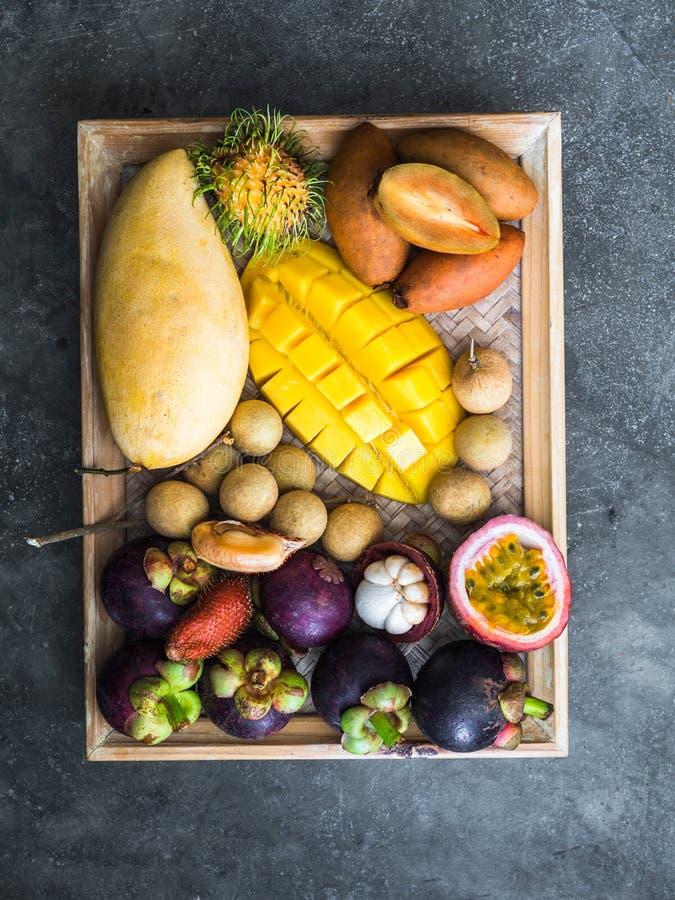 Olika nya thail?ndska frukter - rambutan, mango, mangosteen, longan, sapodilla, passionfrukt, salak, p? ett tr?magasin och ett gr royaltyfri bild