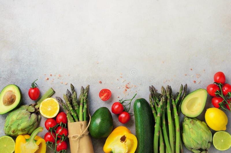 Olika organiska grönsaker - sparriers, tomater körsbäret, avokadot, kronärtskockan, peppar, limefrukt, citron, saltar på grå färg royaltyfri fotografi