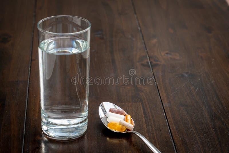 Olika piller är på en sked bredvid ett exponeringsglas av vatten på en brun tabell royaltyfri foto